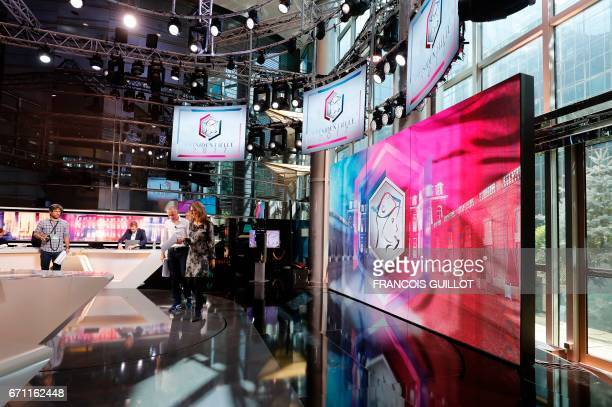 French journalists stand on the set of the French TV channel TF1 on April 21 2017 in BoulogneBillancourt near Paris during a general rehearsal of the...