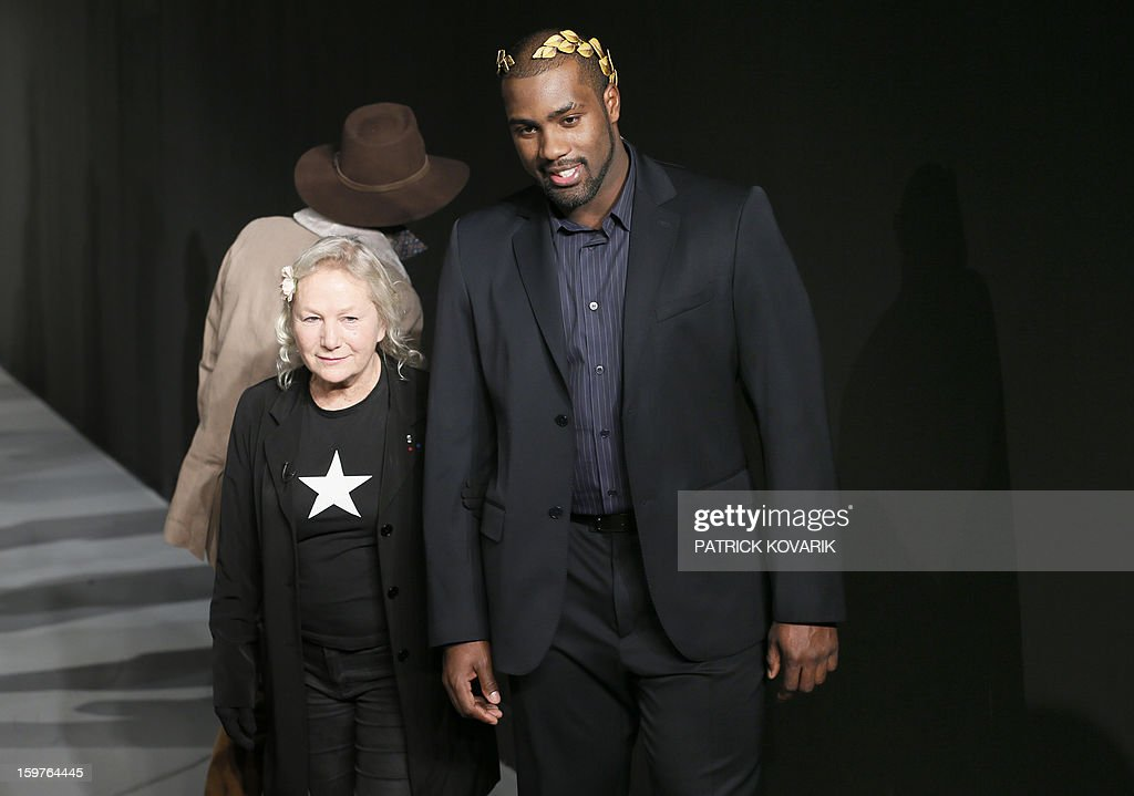 French judo champion Teddy Riner (R) and French designer Agnes B salute the crowd on January 20, 2013 after the presentation of her men's fall-winter 2013-2014 collection at the fashion week in Paris. AFP PHOTO / PATRICK KOVARIK