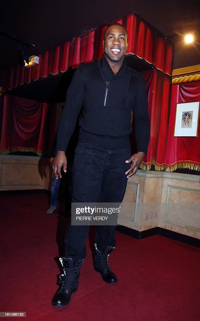 French judoka Teddy Riner arrives to pose next to his wax likeness at the Grevin Museum in Paris on February 11, 2013 during the official presentation of his effigy.