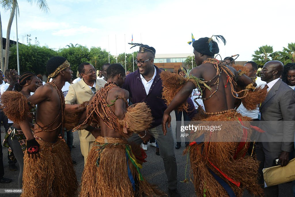 French judoka Teddy Riner dances with traditionnal dancers in the streets of Libreville on May 17 as he arrives to attend the 22nd martial arts night...