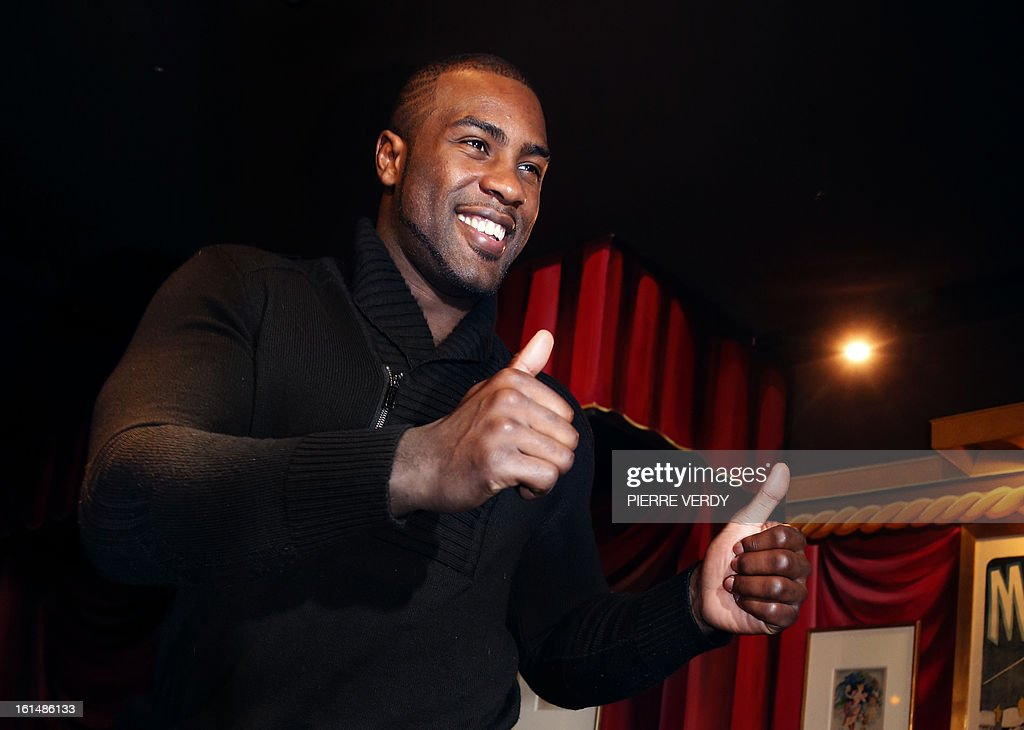 French judoka Teddy Riner gives thumbs up as he arrives to pose next to his wax likeness at the Grevin Museum in Paris on February 11, 2013 during the official presentation of his effigy. AFP PHOTO / PIERRE VERDY