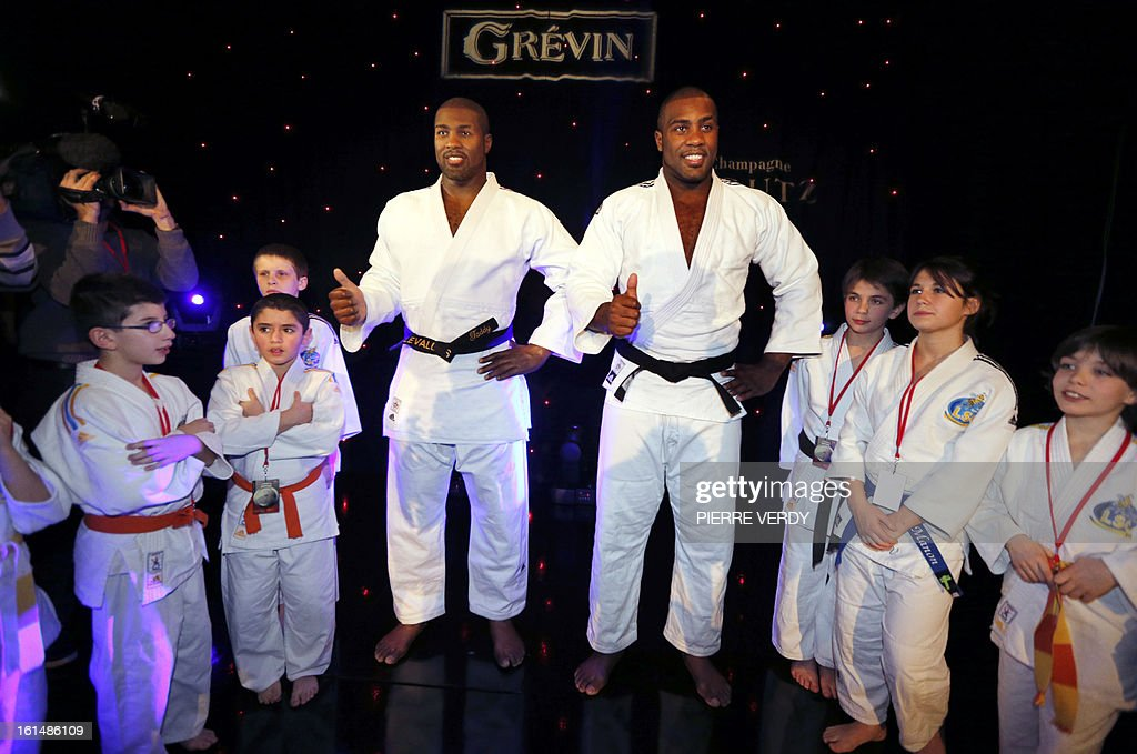 French judoka Teddy Riner (R) poses next to his wax likeness at the Grevin Museum in Paris on February 11, 2013 during the official presentation of his effigy.