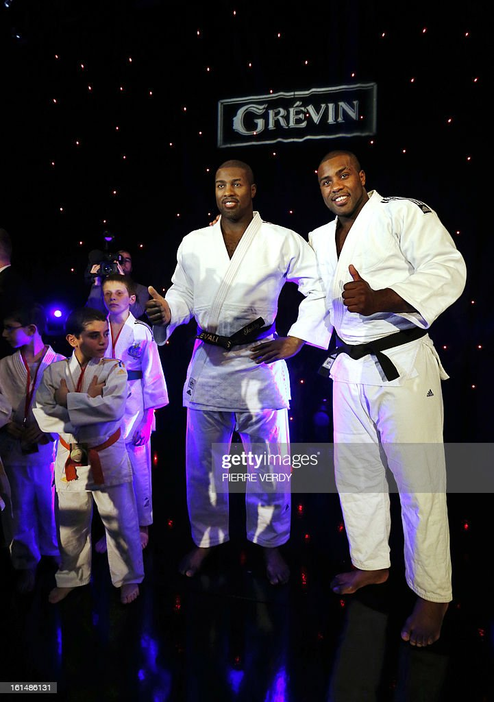 French judoka Teddy Riner (R) poses next to his wax likeness at the Grevin Museum in Paris on February 11, 2013 during the official presentation of his effigy. AFP PHOTO / PIERRE VERDY