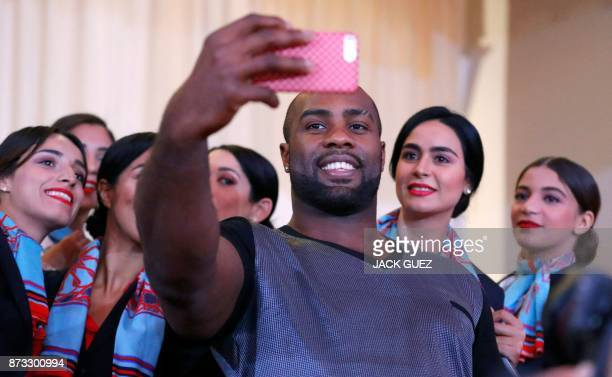 TOPSHOT French judoka Teddy Riner takes a selfie with hostesses after his victory in the Judo World Championships Open in Marrakesh on November 12...
