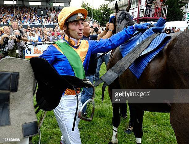 French Julien Zuliani reacts next to his horse horse Martalin after winning on August 27 2013 the yearly Waregem Koerse 'Great Steeple Chase of...