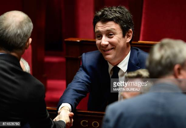 French Junior Economy Minister Benjamin Griveaux shakes hands with another minister during a session of questions to the government at the National...