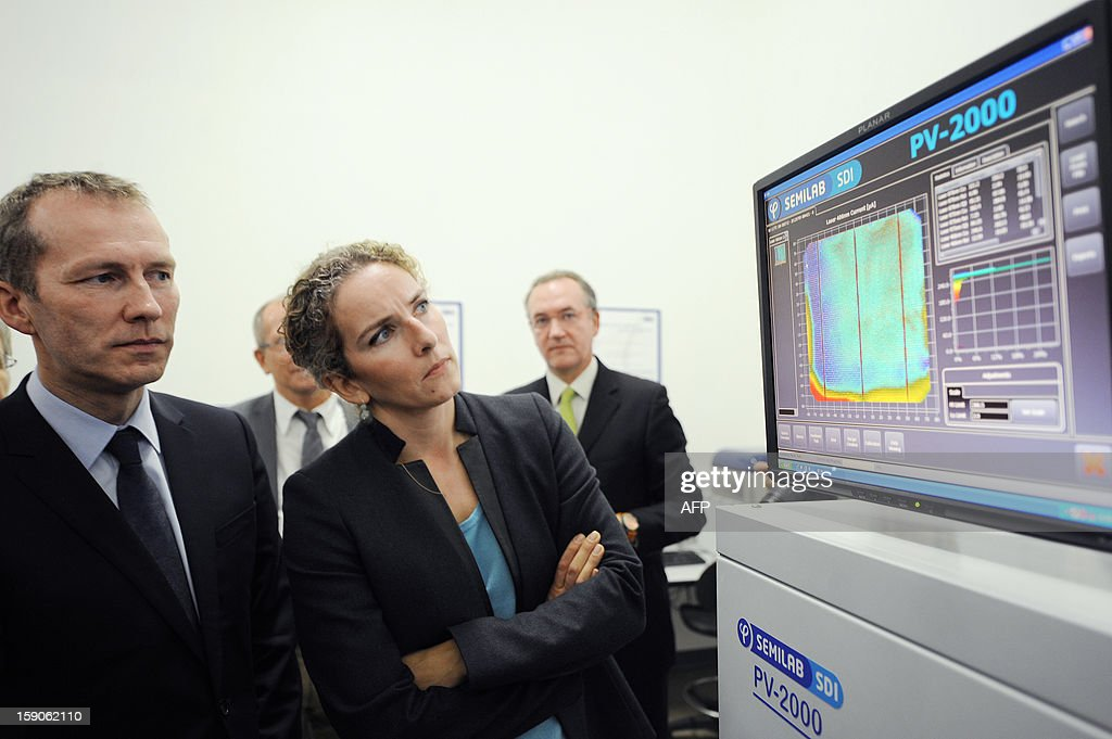 French Junior Minister for Agriculture, Agribusiness and Forest Guillaume Garot (L) and Ecology Minister Delphine Batho (R) look at a monitoring screen as they visit an assembly line of photovoltaic cells at the French MPO Energy plant in Averton, western France, on January 7, 2013.
