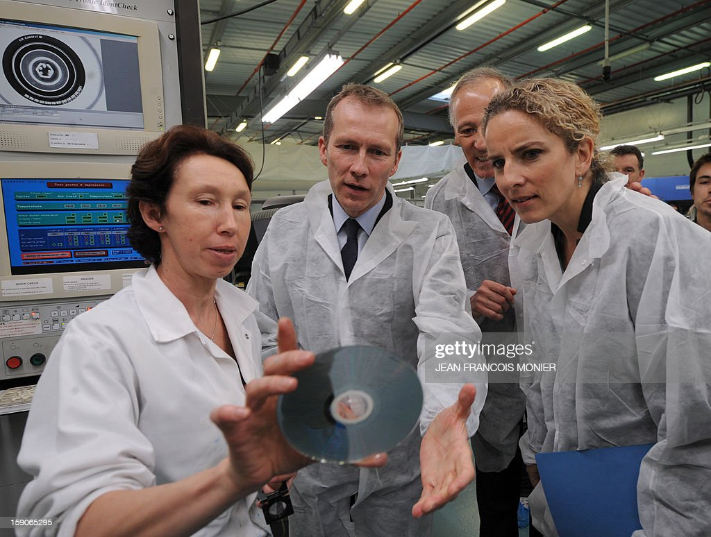 French Junior Minister for Agriculture, Agribusiness and Forest Guillaume Garot (C), the President of the MPO International company Loic De Poix (2ndR) and French Ecology Minister Delphine Batho (R) visit an assembly line of DVD at MPO Industry plant in Villaines-la-Juhel, western France, on January 7, 2013.