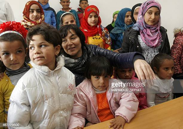 French Junior Minister for Development and FrenchSpeaking Communities minister Annick Girardin is surrounded by students in a classroom during a...