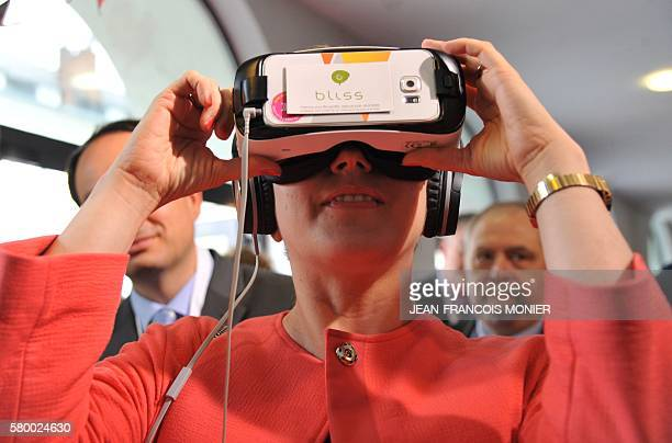 French junior minister for Digital Economy Axelle Lemaire looks through virtual reality glasses as she visits a virtual reality booth on July 25 at...