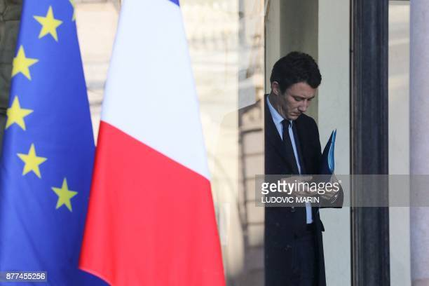 French Junior Minister for Economy Benjamin Griveaux looks at his smartphone as he leaves the Elysee presidential palace after the weekly cabinet...