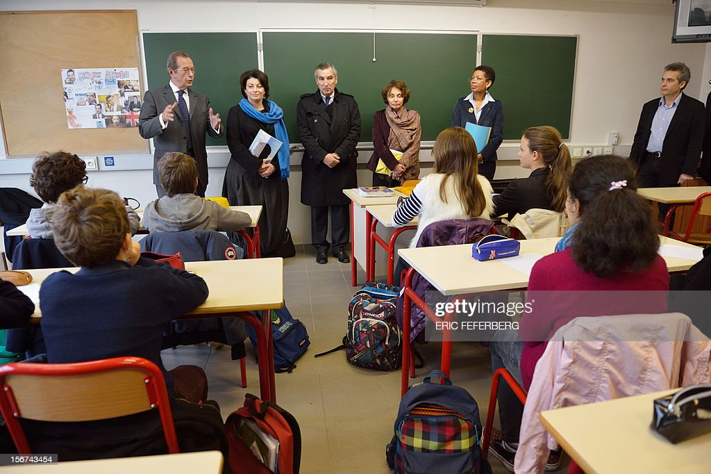 French Junior Minister for Educational Success, George Pau-Langevin (R), Rights defender Dominique Baudis (L) and his deputy and Children defender Marie Derain (2ndL) visit a classroom at the Duruy college for the International Children Rights Day on November 20, 2012 in Paris.
