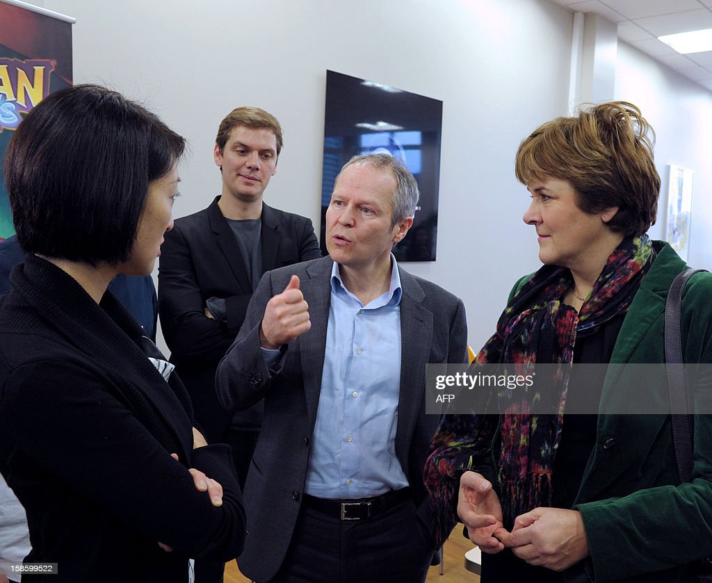 French Junior Minister for SMEs, Innovations and Digital Economy Fleur Pellerin (L) and Dominique Voynet (R), mayor of Montreuil listen to French videogame firm Ubisoft CEO, Yves Guillemot (C) during their visit to Ubisoft's development studio on December 20, 2012 in Montreuil, a Paris' suburb. At left in the background is seen Xavier Poix, head of Ubisoft studios in France. AFP PHOTO / ERIC PIERMONT