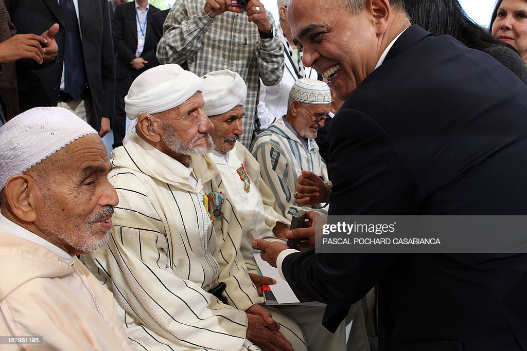 French Junior minister for Veterans Kader Arif (R) gives decorations to Moroccan war veterans, who served as 'Moroccan Goumiers' in the French Army of Africa during WWII, on October 3, 2013 in Bastia during an award ceremony marking the 70th anniversary of the liberation of the French island of Corsica in the Mediterranean Sea.