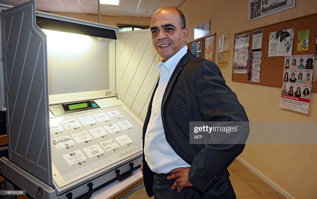 French Junior Minister for Veterans, Kader Arif, Socialist Party (PS) candidate in the 10th constituency of Haute-Garonne for the French parliamentary elections, stands in front of an electronic ballot box during the first round at a polling station on June 10, 2012 in Castanet-Tolosan, southern France. Elections to the French National Assembly take place in two rounds on 10 and 17 June, 2012, following Socialist Francois Hollande's presidential election win last month. GABALDA