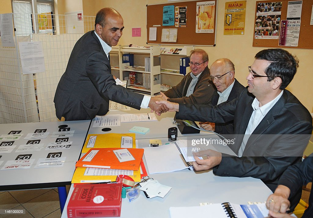 French Junior Minister for Veterans, Kader Arif, Socialist Party (PS) candidate in the 10th constituency of Haute-Garonne for the French parliamentary elections, shakes hands with a scutineer prior to cast his vote during the first round at a polling station on June 10, 2012 in Castanet-Tolosan, southern France. Elections to the French National Assembly take place in two rounds on 10 and 17 June, 2012, following Socialist Francois Hollande's presidential election win last month. GABALDA