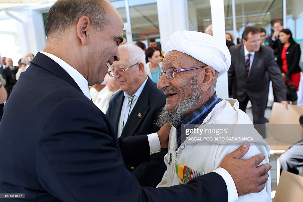 French Junior minister for Veterans Kader Arif (L) speaks with a Moroccan war veteran, who served as 'Moroccan Goumiers' in the French Army of Africa during WWII, on October 3, 2013 in Bastia during an award ceremony marking the 70th anniversary of the liberation of the French island of Corsica in the Mediterranean Sea.