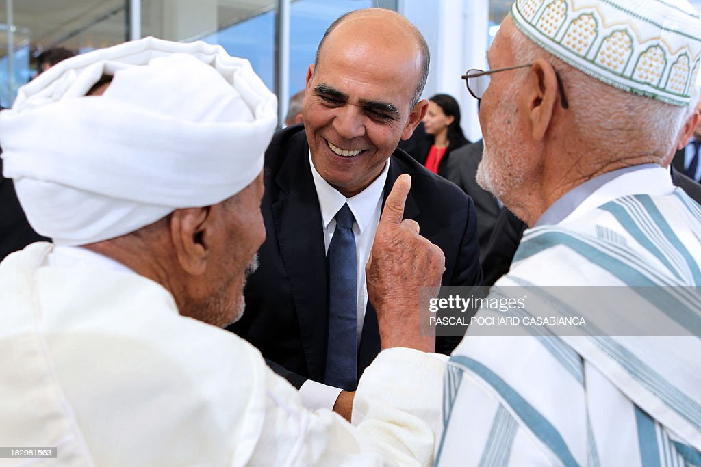 French Junior minister for Veterans Kader Arif (C) speaks with Moroccan war veterans, who served as 'Moroccan Goumiers' in the French Army of Africa during WWII, on October 3, 2013 in Bastia during an award ceremony marking the 70th anniversary of the liberation of the French island of Corsica in the Mediterranean Sea.