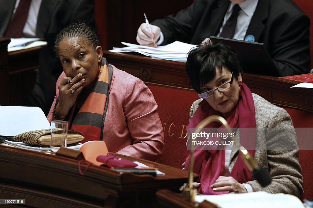French Justice Minister Christiane (L) and Junior Minister for Family Dominique Bertinotti listen during the debate to allow gay couples to get married and adopt children on February 5, 2013 at the National Assembly in Paris. Three days before, members of Parliament voted 249-97 in favour of Article One of the draft law, which redefines marriage as being a contract between two people rather than necessarily between a man and a woman. AFP PHOTO FRANCOIS GUILLOT