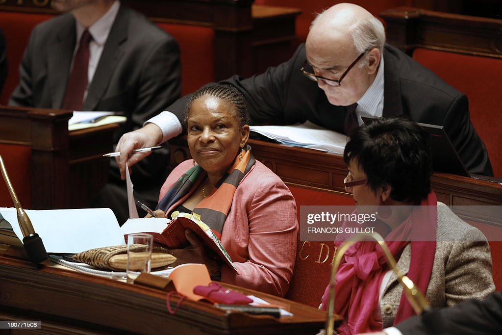 French Justice Minister Christiane Taubira (C) and her head of staff Christian Vigouroux (top) look at a civil code during the debate to allow gay couples to get married and adopt children on February 5, 2013 at the National Assembly in Paris. Three days before, members of Parliament voted 249-97 in favour of Article One of the draft law, which redefines marriage as being a contract between two people rather than necessarily between a man and a woman. AFP PHOTO FRANCOIS GUILLOT
