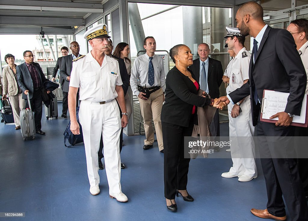 French Justice Minister Christiane Taubira (C), flanked by the French overseas territory of Guiana's Prefect Denis Labbe (C), shakes hand with an unidentified man as she arrives on February 21, 2013 at the Cayenne's airport in Matoury, to begin a five-day official visit in Guiana.