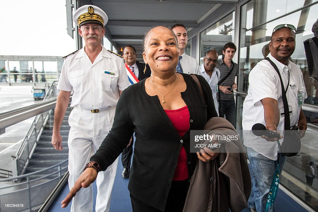 French Justice Minister Christiane Taubira (C) is flanked by the French overseas territory of Guiana's Prefect Denis Labbe (L)as she arrives on February 21, 2013 at the Cayenne's airport in Matoury, to begin a five-day official visit in Guiana.