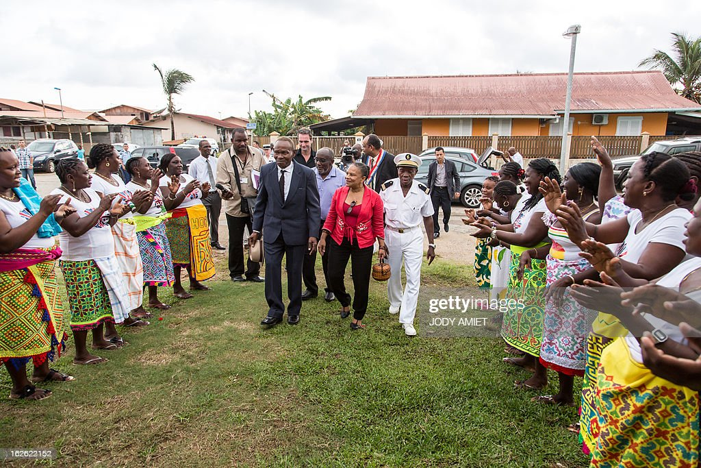 French Justice minister Christiane Taubira (C) is welcomed by inhabitants as she visits the neighbourhood of Saramaca, on February 23, 2013 in Kourou, as part of her five-day visit to the French French overseas territory of Guiana.