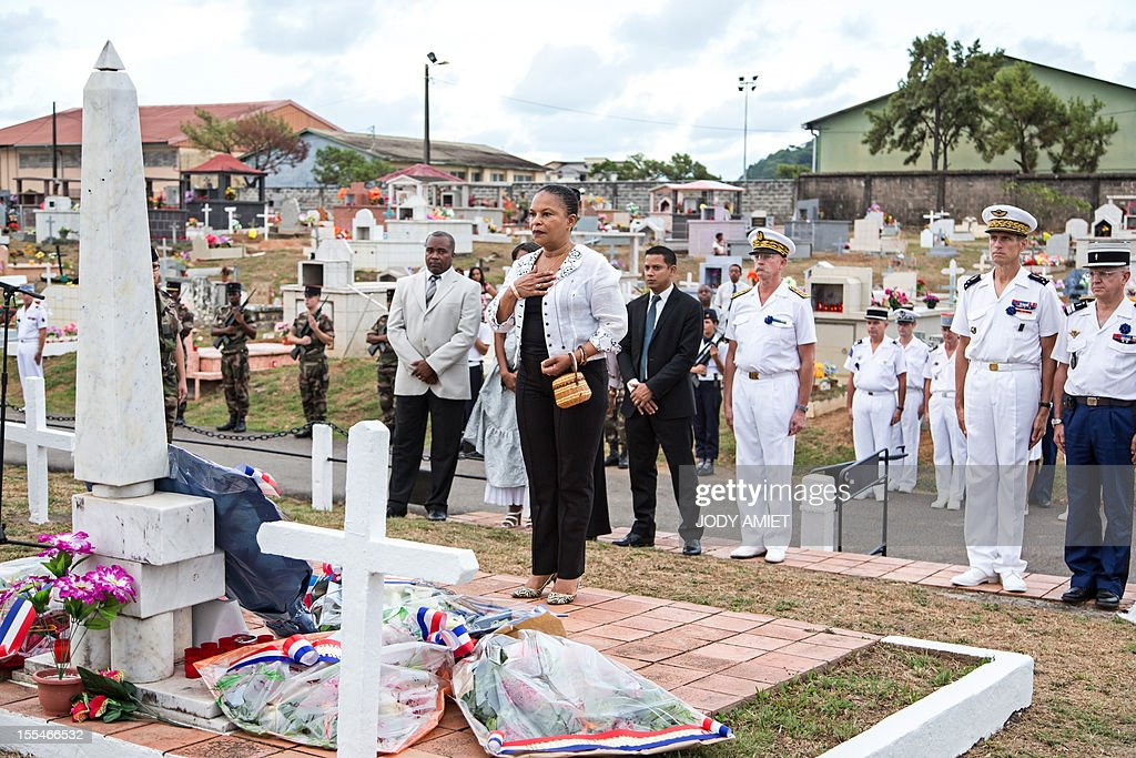 French Justice Minister Christiane Taubira (C) pays respect after laying a wreath, on November 2, 2012, in the military section of Cayenne's cemetery, in French overseas region of Guiana, during a ceremony of remembrance dedicated to soldiers and war victims. Behind Christiane Taubira are seen General Bernard Metz (2ndR), commander of the Armed Forces in French Guiana and the Prefect of Guiana, Denis Labbe (3thR).
