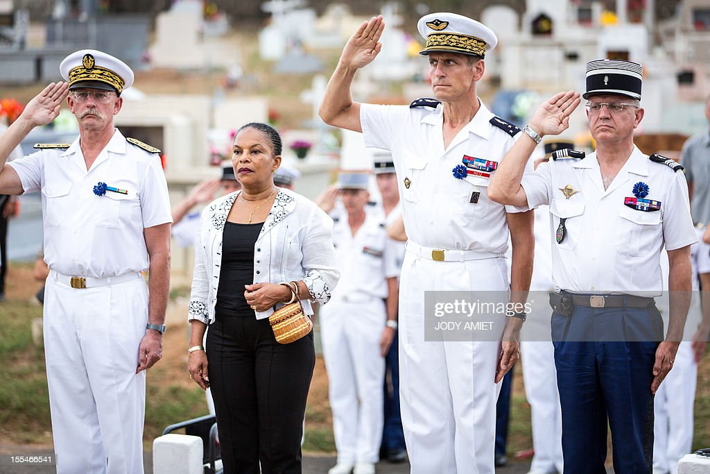 French Justice Minister Christiane Taubira (2ndL) pays respect after laying a wreath, surrounded by the Prefect of Guiana, Denis Labbe (L) and General Bernard Metz (2ndR), commander of the Armed Forces in French Guiana, on November 2, 2012, in the military section of Cayenne's cemetery, in French overseas region of Guiana, during a ceremony of remembrance dedicated to soldiers and war victims.