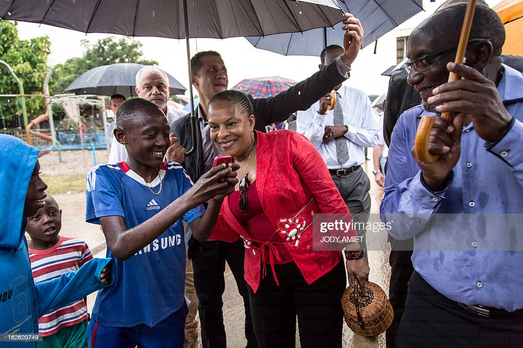 French Justice minister Christiane Taubira (C) pose for children as she visits the neighbourhood of Saramaca, on February 23, 2013 in Kourou, as part of her five-day visit to the French French overseas territory of Guiana.
