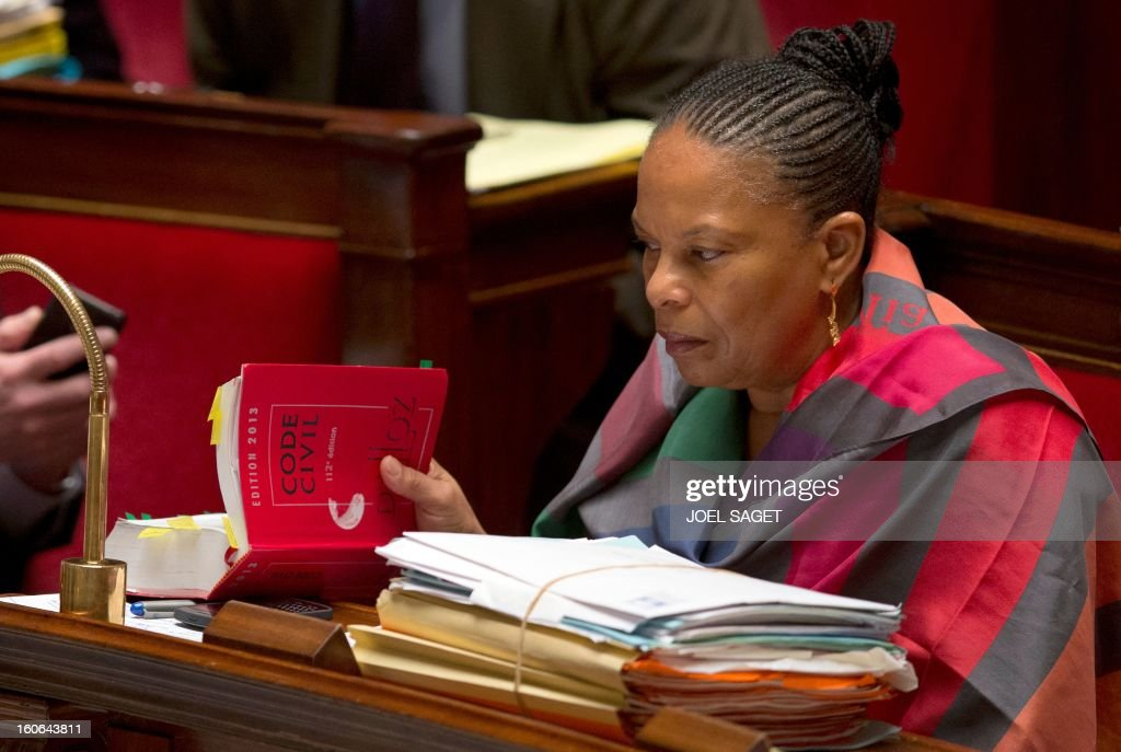 French Justice Minister Christiane Taubira reads a civil code while taking part in the debate to allow gay couples to get married and adopt children on February 4, 2013 at the National Assembly in Paris. Two days before, Members of Parliament voted 249-97 in favour of Article One of the draft law, which redefines marriage as being a contract between two people rather than necessarily between a man and a woman. AFP PHOTO JOEL SAGET