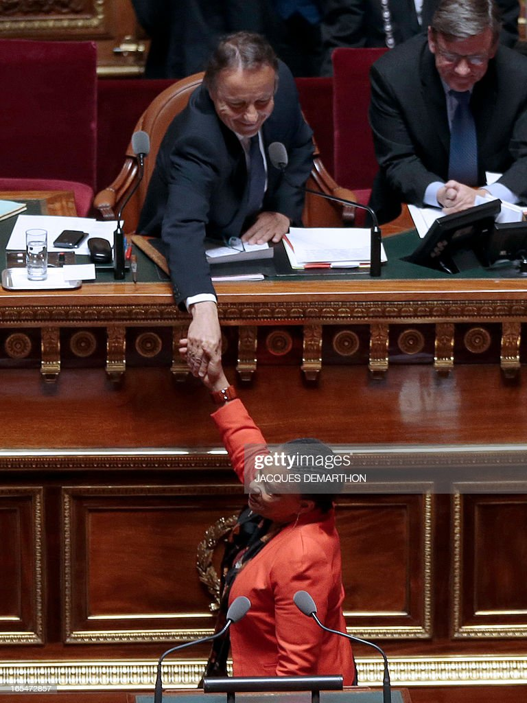French Justice minister Christiane Taubira (down) shakes hands with French Senate president Jean-Pierre Bel at the semicircle of the French Senate in Paris, on April 4, 2013, on the first day of the debate on the controversial bill to legalise same-sex marriage and adoption. While the upper house is unlikely to reject the groundbreaking reform, it is still expected to be a tight vote as the ruling Socialists enjoy a smaller majority in the Senate than in the National Assembly.