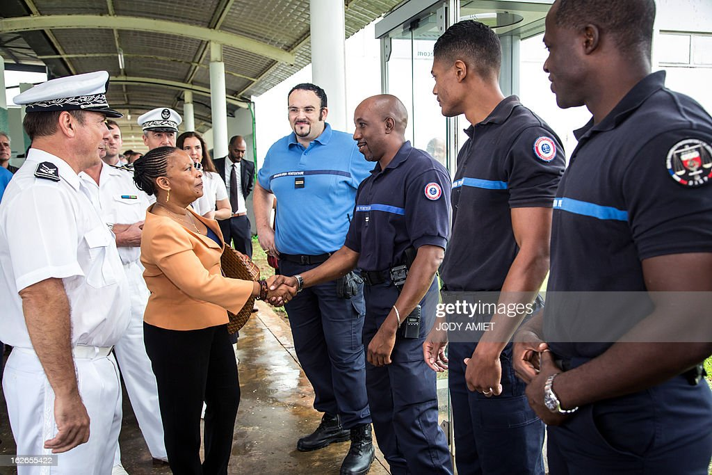French Justice minister Christiane Taubira shakes hands with prison guards as she visits the prison of Remire-Montjoly with Daniel Willemot (L), head of the prison on February 25, 2013, in the French overseas territory of Guiana.