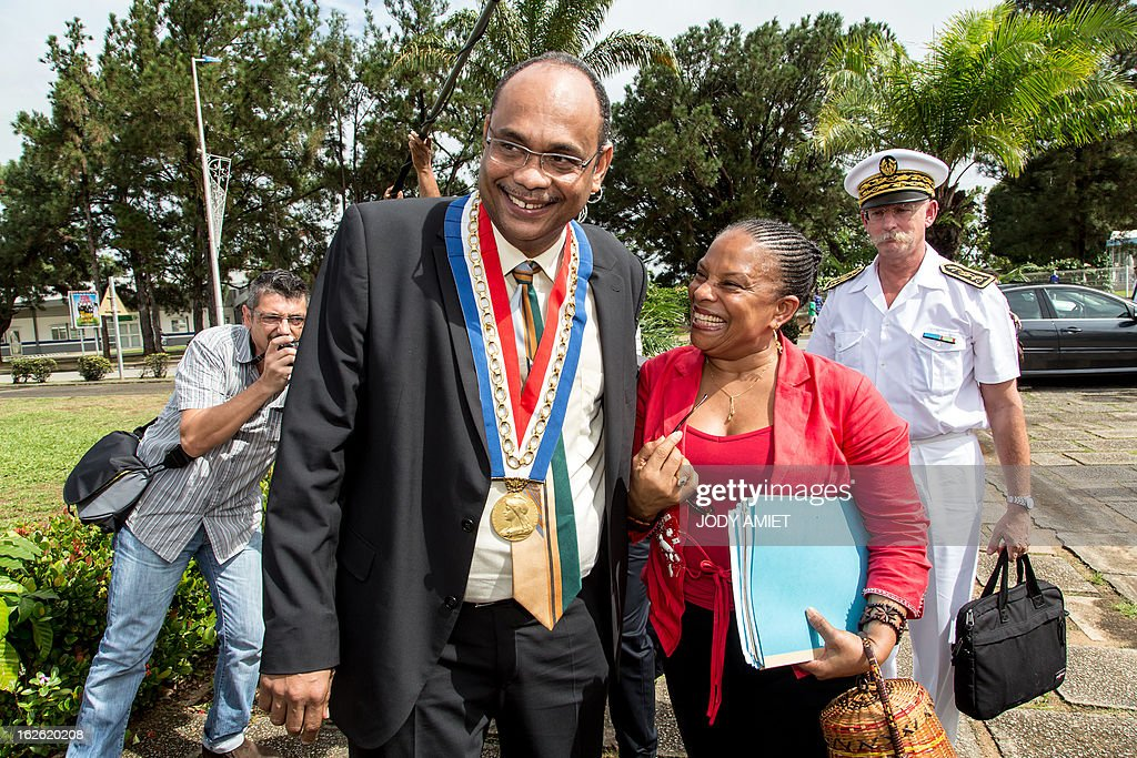 French Justice minister Christiane TAubira (2ndR) shares a laugh with Kourou's mayor Jean-Etienne Antoinette (C) prior to a meeting at Kourou's city hall, on February 23, 2013, as part of her five-day visit to the French French overseas territory of Guiana.