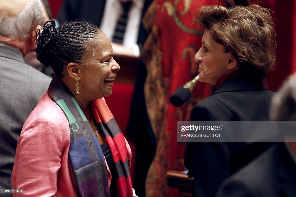 French Justice Minister Christiane Taubira (L) smiles as she leaves for a break with French Junior Minister for the Elderly and Disabled, Michele Delaunay, during the debate to allow gay couples to get married and adopt children on February 5, 2013 at the National Assembly in Paris. Three days before, members of Parliament voted 249-97 in favour of Article One of the draft law, which redefines marriage as being a contract between two people rather than necessarily between a man and a woman. AFP PHOTO FRANCOIS GUILLOT