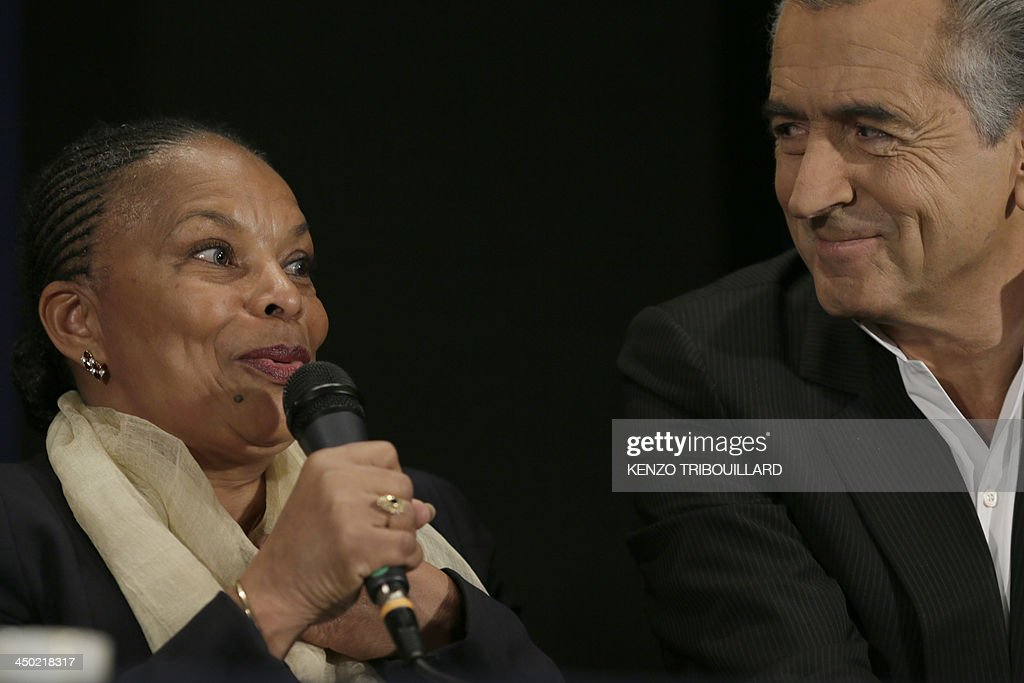 French Justice minister Christiane Taubira (L) speaks next to French philosopher and writer Bernard-Henri Levy during a meeting to support Taubira after she was the target of multiple racist insults, on November 17, 2013 in Paris.
