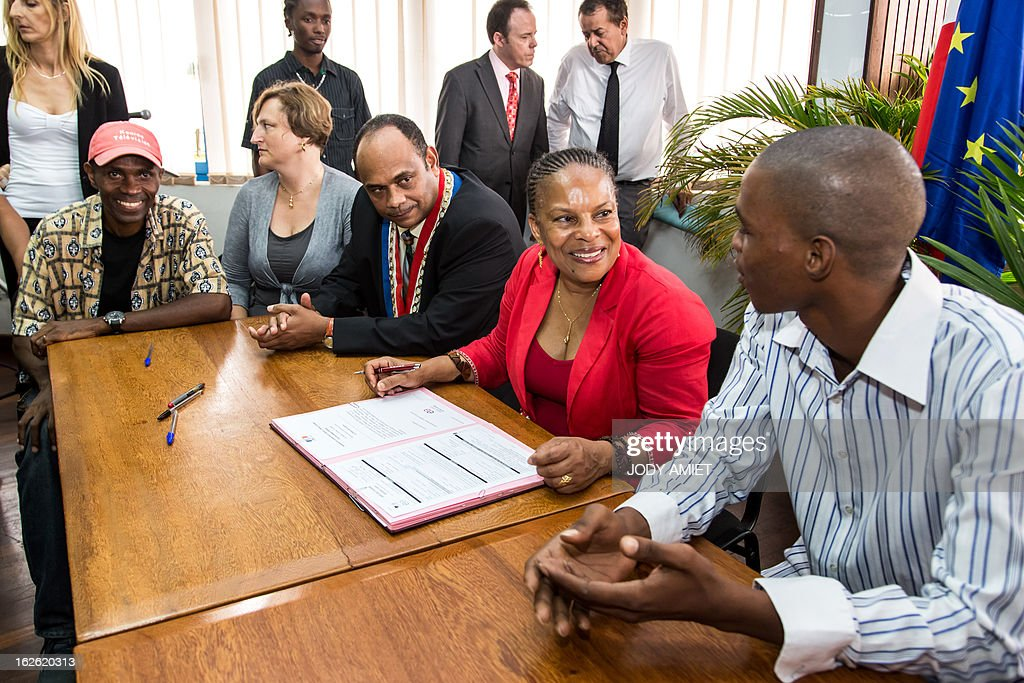 French Justice minister Christiane Taubira (C) speaks with a young man eyed by Kourou's mayor Jean-Etienne Antoinette (3rdR) as she signs several Emploi d'avenir (Job futures) convention during a meeting at Kourou's city hall, on February 23, 2013, as part of her five-day visit to the French French overseas territory of Guiana.