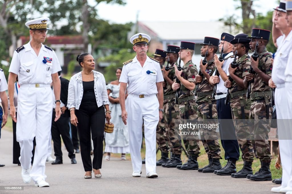 French Justice Minister Christiane Taubira (C), surrounded by General Bernard Metz (C,L), commander of the Armed Forces in French Guiana and the Prefect of Guiana, Denis Labbe (C,R), reviews troops on November 2, 2012 in the military section of Cayenne's cemetery, in French overseas region of Guiana, during a ceremony of remembrance dedicated to soldiers and war victims.