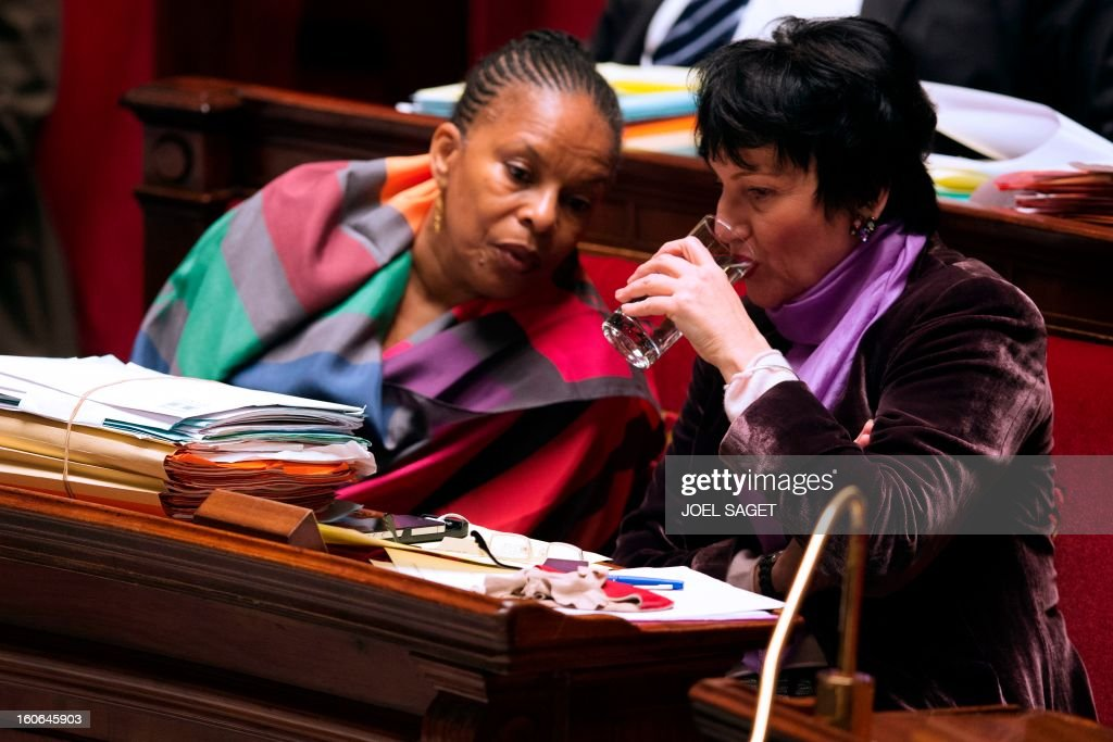 French Justice Minister Christiane Taubira (L) talks to Junior Minister for Family Dominique Bertinotti while taking part in the debate to allow gay couples to get married and adopt children on February 4, 2013 at the National Assembly in Paris. Two days before, Members of Parliament voted 249-97 in favour of Article One of the draft law, which redefines marriage as being a contract between two people rather than necessarily between a man and a woman.