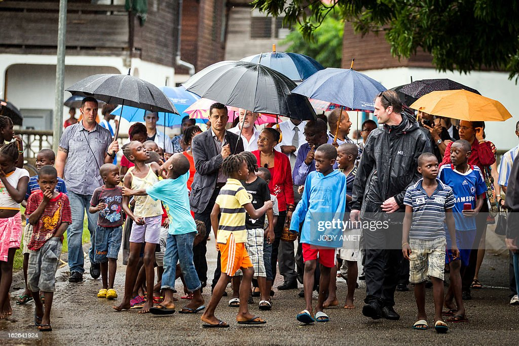French Justice minister Christiane Taubira (C) walks in a street, surrounded by children, as she visits the neighbourhood of Saramaca on February 25, 2013 in Kourou, as part of her five-day visit to the French overseas territory of Guiana. AFP PHOTO JODY AMIET