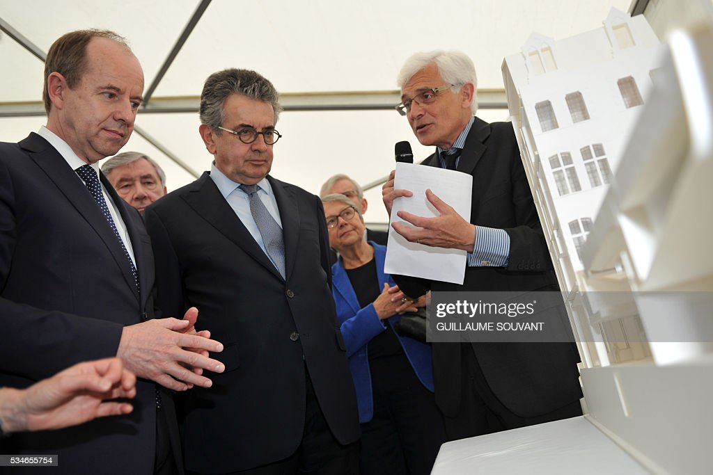 French Justice Minister Jean-Jacques Urvoas (L) flanked by mayor of Poitiers Alain Clayes (C) looks at a model of the futur courthouse of Poitiers, western France, during his visit of the site on May 27, 2016. / AFP / GUILLAUME