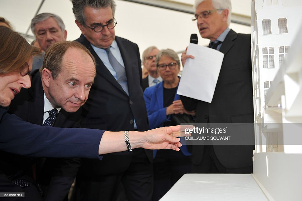 French Justice Minister Jean-Jacques Urvoas (2ns L) flanked by mayor of Poitiers Alain Clayes (C) looks at a model of the futur courthouse of Poitiers, western France, during his visit of the site on May 27, 2016. / AFP / GUILLAUME