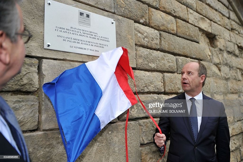 French Justice Minister Jean-Jacques Urvoas (R) flanked by mayor of Poitiers Alain Clayes (L) unveils an inauguration plaque for the construction of the futur courthouse of Poitiers, western France, during his visit of the site on May 27, 2016. / AFP / GUILLAUME