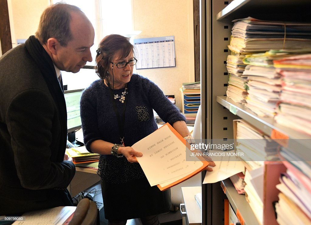 French Justice Minister Jean-Jacques Urvoas (L) looks at the pending files and talks to a court clerk during his visit to the Regional Court (TGI) of Chartres on February 12, 2016. / AFP / JEAN-FRANCOIS MONIER