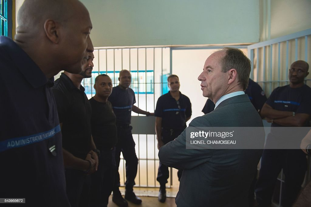 French Justice Minister Jean-Jacques Urvoas (R) meets with prison wardens as he tours the Ducos prison with prison director Bruno Coulon (2nd R) on June 30, 2016 during the inauguration of the extension of the Ducos prison in Ducos, near Fort-de-france, on the Caribbean island of Martinique. / AFP / Lionel CHAMOISEAU