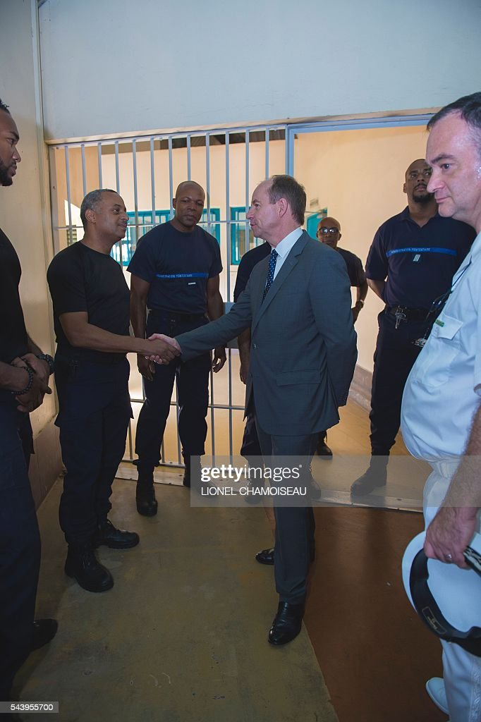 French Justice Minister Jean-Jacques Urvoas (C) meets with prison wardens as he tours the Ducos prison with prison director Bruno Coulon (2nd R) on June 30, 2016 during the inauguration of the extension of the Ducos prison in Ducos, near Fort-de-france, on the Caribbean island of Martinique. / AFP / Lionel CHAMOISEAU