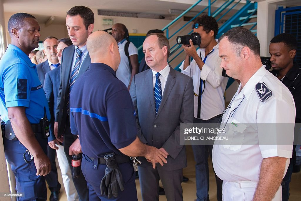 French Justice Minister Jean-Jacques Urvoas (C) meets with prison wardens as he tours the Ducos prison with prison director Bruno Coulon (R) on June 30, 2016 during the inauguration of the extension of the Ducos prison in Ducos, near Fort-de-france, on the Caribbean island of Martinique. / AFP / Lionel CHAMOISEAU