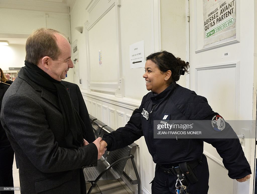 French Justice Minister Jean-Jacques Urvoas (L) shakes hand with a police officer during his visit to the Regional Court (TGI) of Chartres on February 12, 2016. / AFP / JEAN-FRANCOIS MONIER