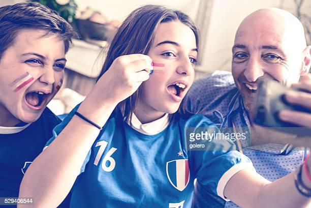 Français Enfants en tenue de ventilateur de football et père prenant une autophoto