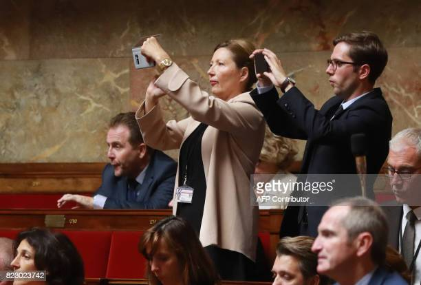 French La Republique en Marche party members of Parliament Natalia Pouzyreff and PieyreAlexandre Anglade take photos during a session of questions to...